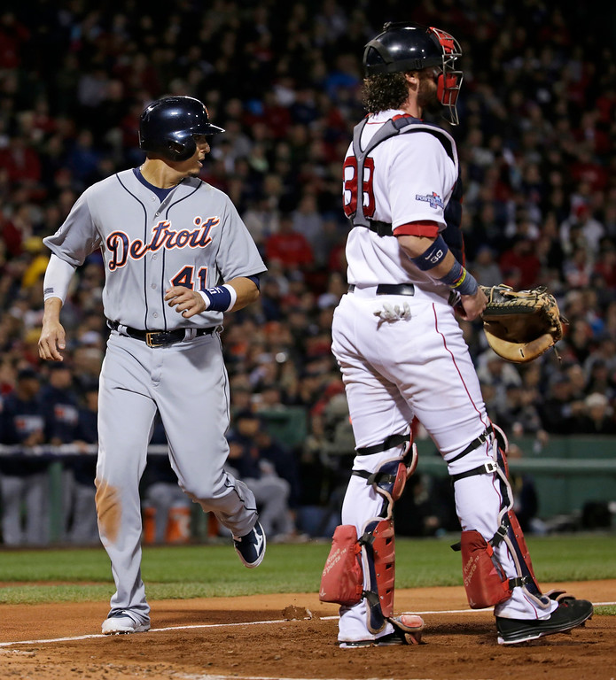 Description of . Detroit Tigers' Victor Martinez scores on a hit by Alex Avila in the second inning as Boston Red Sox's Jarrod Saltalamacchia stands on at home plate during Game 2 of the American League baseball championship series Sunday, Oct. 13, 2013, in Boston. (AP Photo/Charles Krupa)