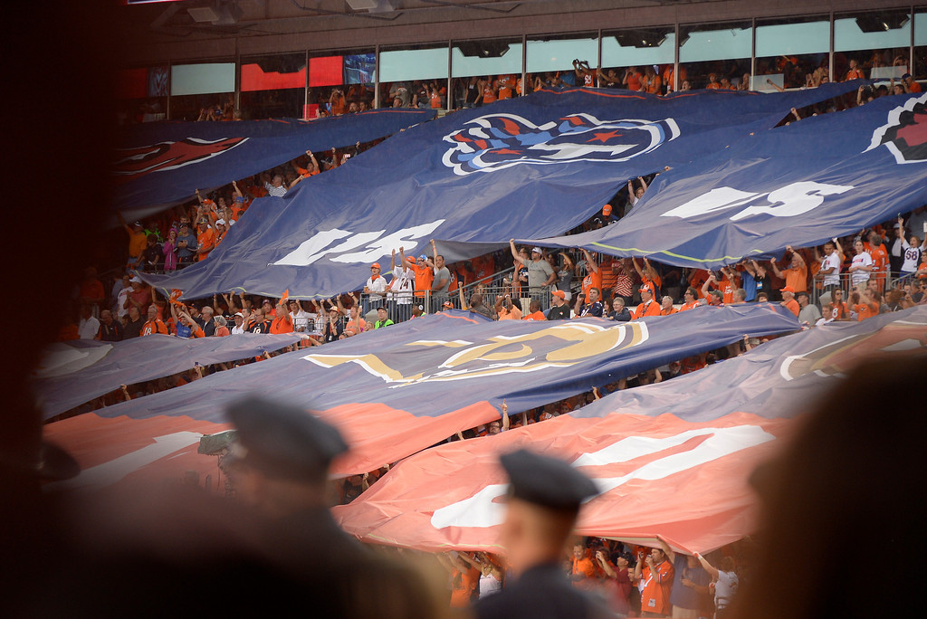 Description of . Fans unravel team flags before the start of the game. The Denver Broncos took on the Baltimore Ravens in the first game of the 2013 season at Sports Authority Field at Mile High in Denver on September 5, 2013. (Photo by Joe Amon/The Denver Post)