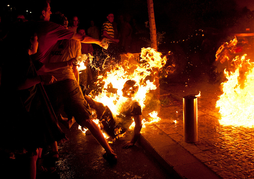 Description of . In this July 14, 2012 file photo, people try to extinguish the fire after a man set himself alight in Tel Aviv, Israel during rally marking the anniversary of a wave of demonstrations that swept the country to protest the high cost of living and other social issues. He was later rushed to a hospital where he was being treated for serious burns, police said.  (AP Photo/Ben Kelmer, File)