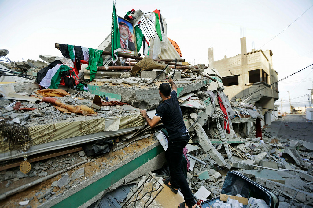 Description of . A Palestinian walks on the rubble of the house of the top Hamas leader in Gaza, Ismail Haniyeh, hit by a pre-dawn Israeli strike, in Gaza City, northern Gaza Strip, Tuesday, July 29, 2014.  (AP Photo/Lefteris Pitarakis)