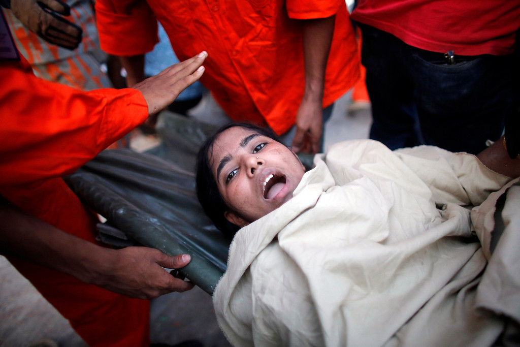 Description of . A garment worker reacts after being rescued by workers after the Rana Plaza building collapsed, in Savar, 30 km (19 miles) outside Dhaka April 24, 2013. REUTERS/Andrew Biraj