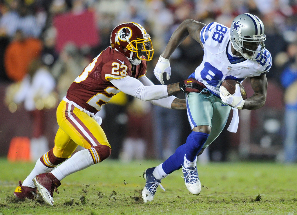 . Dallas Cowboys wide receiver Dez Bryant (88) is stopped by Washington Redskins cornerback DeAngelo Hall (23) during the first half of an NFL football game Sunday, Dec. 30, 2012, in Landover, Md. (AP Photo/Nick Wass)