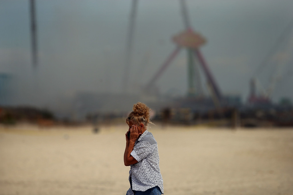 Description of . A woman stands at the scene of a massive fire that destroyed dozens of businesses along an iconic Jersey shore boardwalk on September 13, 2013 in Seaside Heights, New Jersey.   (Photo by Spencer Platt/Getty Images)
