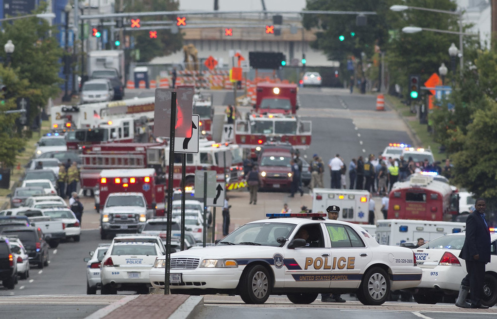 Description of . Police and firefighters respond to the report of a shooting at the Navy Yard in Washington, DC, September 16, 2013.  A gunman shot and wounded at least one person Monday in a headquarters building at the US Navy Yard in Washington and is still at large, the navy said.