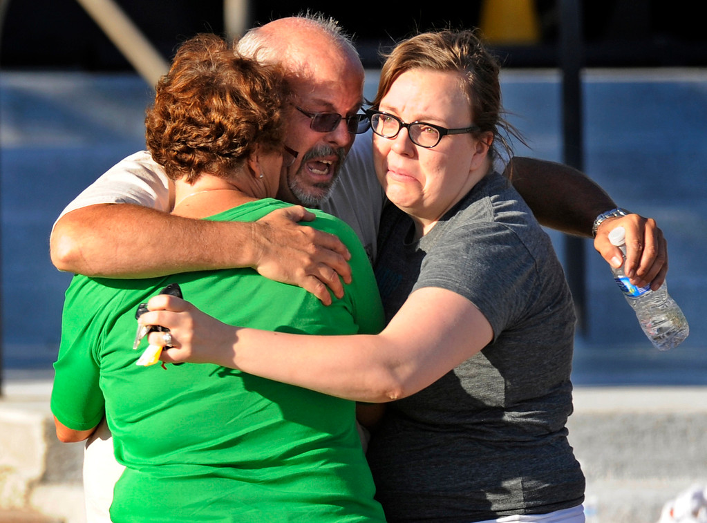 Description of . Tom Sullivan, center, hugs his wife Terry, left, and daughter Megan outside Gateway High School, Friday July 20, 2012, in Aurora. Sullivan is still missing his son, who he said was at the movies where about 50 people were shot 12 fatally early Friday in Aurora. RJ Sangosti, The Denver Post