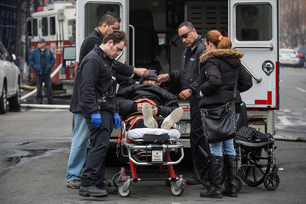 Description of . A man is loaded into an ambulance on a stretcher hours after a two-building collapse on March 12, 2014 in New York City.   (Photo by Andrew Burton/Getty Images)