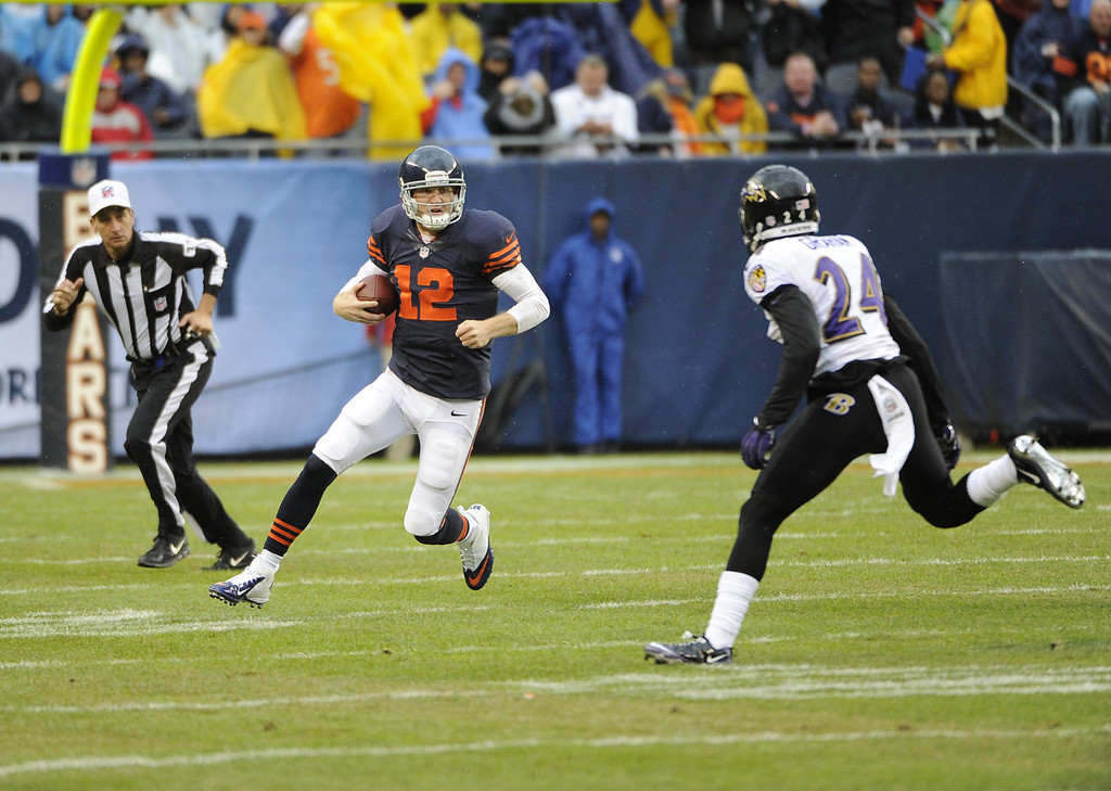 Description of . Josh McCown #12 of the Chicago Bears runs as Corey Graham #24 of the Baltimore Ravens looks to make a tackle during the first quarter on November 17, 2013 at Soldier Field in Chicago, Illinois. (Photo by David Banks/Getty Images)