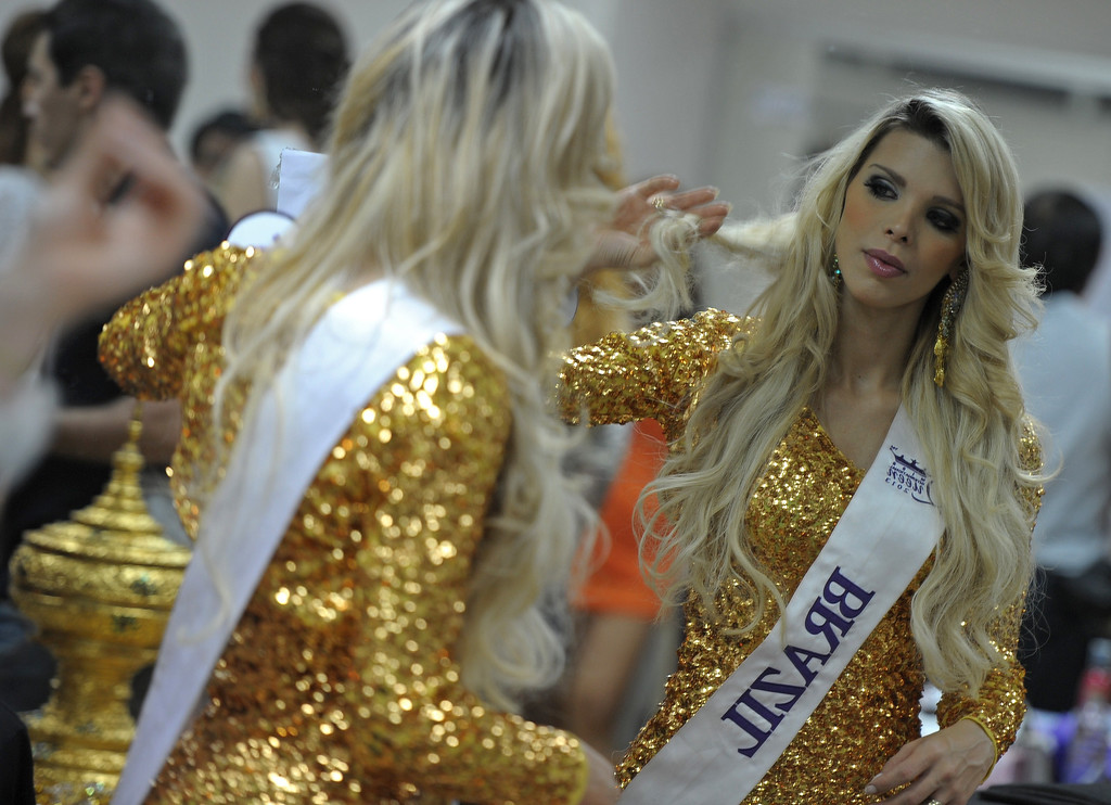 Description of . A contestant poses in front mirror at backstage during the Miss International Queen 2013 beauty contest in Pattaya resort on November 1, 2013. Twenty-five contestants from 17 countries are to compete in Pattaya for the crown of Miss International Queen since 2004. AFP PHOTO / PORNCHAI KITTIWONGSAKUL/AFP/Getty Images