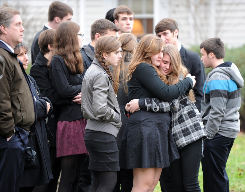 Description of . Mourners embrace following services for six year-old Noah Pozner, who was killed in the December 14, 2012 shooting massacre in Newtown, Connecticut, at Abraham L. Green and Son Funeral Home on December 17, 2012 in Fairfield, Connecticut. Today is the first day of funerals for some of the twenty children and seven adults who were killed by 20-year-old Adam Lanza on December 14, 2012.  AFP PHOTO / Don EMMERT/AFP/Getty Images