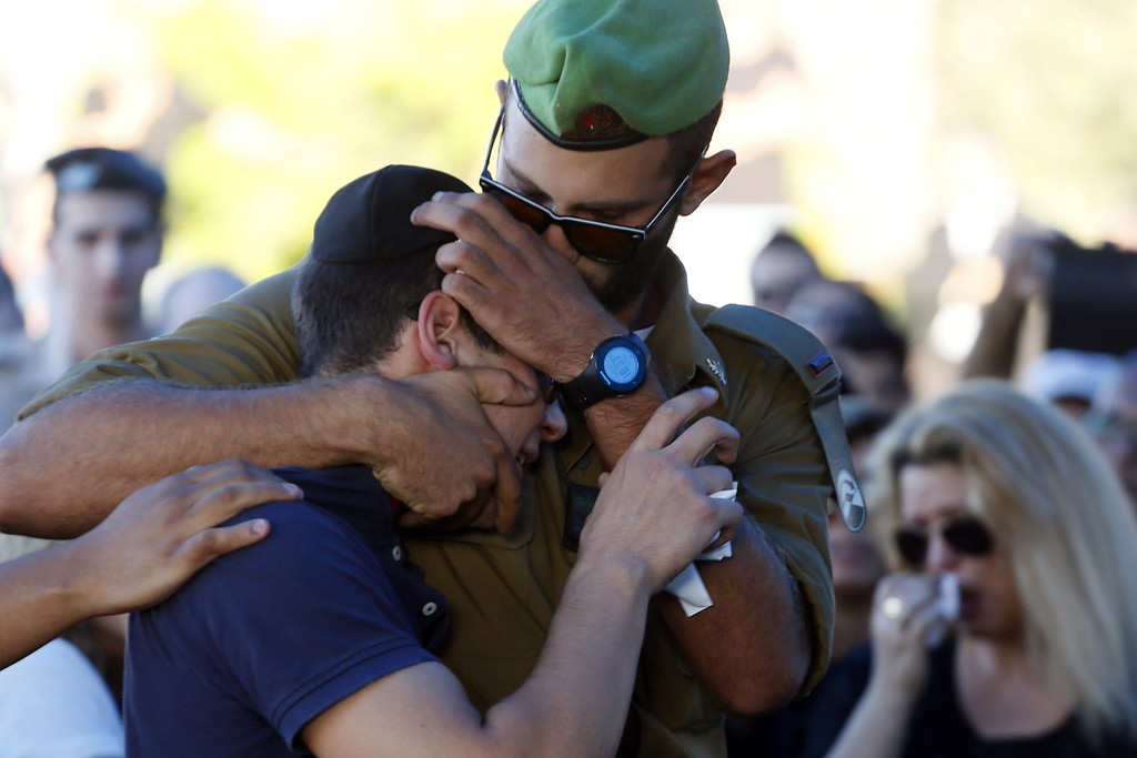 Description of . Friends of 21-year-old Israeli St.-Sgt. Matan Gotlib, mourn during his funeral at the military cemetery in the Israeli costal city of Rishon Letzion on July 31, 2014, after he was killed the previous day in combat in the Gaza Strip. Israel said it would not pull troops from Gaza until they finish destroying a network of cross-border tunnels, and the army confirmed mobilizing another 16,000 additional reservists, hiking the total number called up to 86,000. AFP PHOTO/ GALI TIBBON/AFP/Getty Images