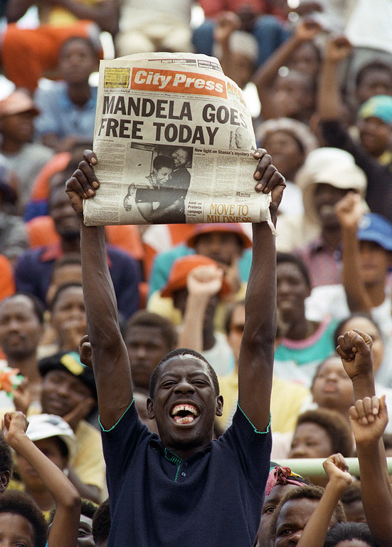 Description of . A jubilant Sowetan holds up 11 February 1990 in Soweto a newspaper announcing the release of anti-apartheid leader and member of the African National Congress (ANC) Nelson Mandela, at a mass ANC rally. South African President de Klerk lifted 02 February the 30-year-old ban on the ANC and the South African Communikst Party, and 11 February, Nelson Mandela walked out of Victor Vester prison, near Cape Town, after 26 year since he  was sentenced to life imprisonment. (Photo credit should read TREVOR SAMSON/AFP/Getty Images)