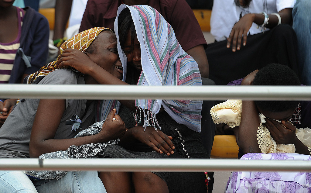 Description of . Women cry at the Amahoro stadium in Kigali, on April 7,2014, as they attend a ceremony marking the 20th anniversary of Rwanda's genocide. Rwandan President Paul Kagame took a thinly-veiled swipe at France on April 7, saying it was impossible to