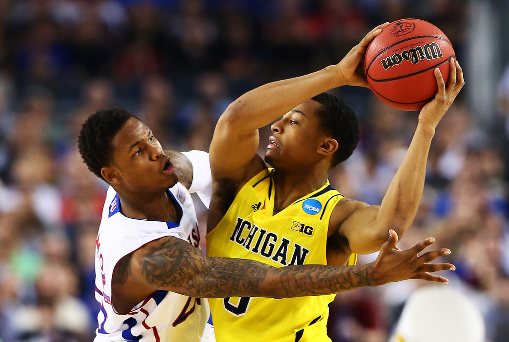 Description of . ARLINGTON, TX - MARCH 29:  Ben McLemore #23 of the Kansas Jayhawks defends against Trey Burke #3 of the Michigan Wolverines in the first half during the South Regional Semifinal round of the 2013 NCAA Men\'s Basketball Tournament at Dallas Cowboys Stadium on March 29, 2013 in Arlington, Texas.  (Photo by Tom Pennington/Getty Images)