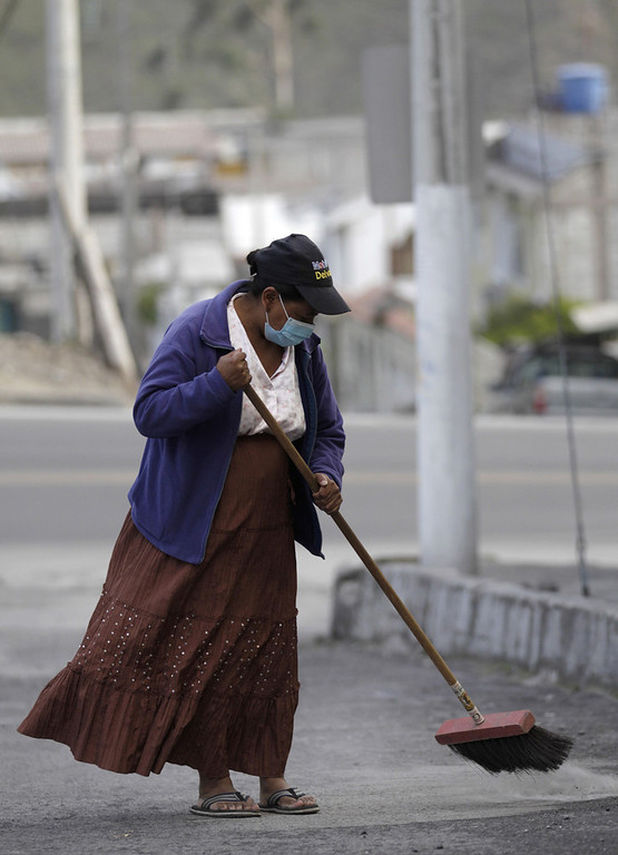 Description of . A woman sweeps up volcanic ash spewed from the nearby Tungurahua volcano in, Banos, Ecuador, Monday, Dec. 17, 2012. The country's National Geophysics Institute says that a constant plume of gas and ash is rising about half a mile (1 kilometer) above the crater, with ash falling on nearby communities.  (AP Photo/Dolores Ochoa)