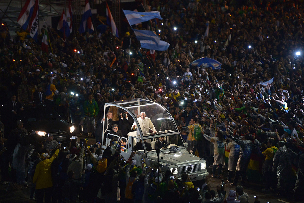 Description of . Pope Francis arrives on the popemobile at Rio de Janeiro's iconic Copacabana beachfront on July 25, 2013 for his welcome to World Youth Day ceremonies. On the fourth day of his visit to Brazil and borne along by adoring crowds, Pope Francis waded into the country's ramshackle slums and onto the front line of its fierce national battle over poverty and corruption, before going to the much wealthier district of Copacabana for his welcome by the youth.   GABRIEL BOUYS/AFP/Getty Images