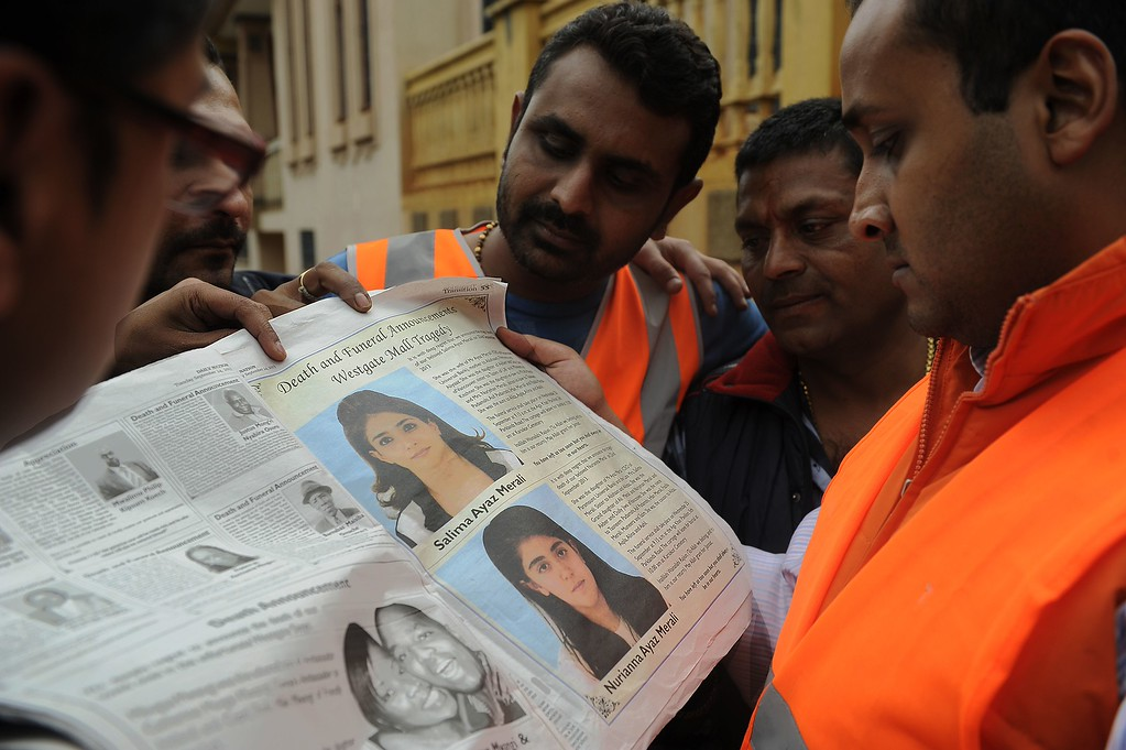 Description of . Members of the Indian community look at a newspaper bearing funeral arrangements of victims of the Westgate mall terrorist attack in Nairobi, on September 24, 2013.  AFP PHOTO / SIMON MAINA/AFP/Getty Images