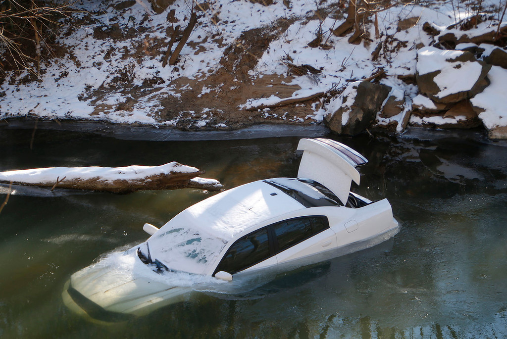 Description of . A car lies half submerged in the Cahaba River Thursday Jan.30,  2014,. in Mountain Brook,  Ala. The driver was able to escape before the car slid into the river during Tuesday's snow storm and was not injured. (AP Photo/Hal Yeager)