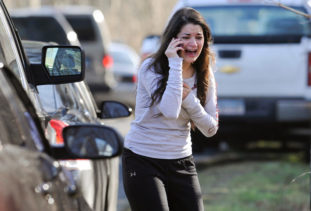 Description of . A woman waits to hear about her sister, a teacher, following a shooting at the Sandy Hook Elementary School in Newtown, Conn., about 60 miles (96 kilometers) northeast of New York City, Friday, Dec. 14, 2012. An official with knowledge of Friday's shooting said 27 people were dead, including 18 children. It was the worst school shooting in the country's history. (AP Photo/Jessica Hill)