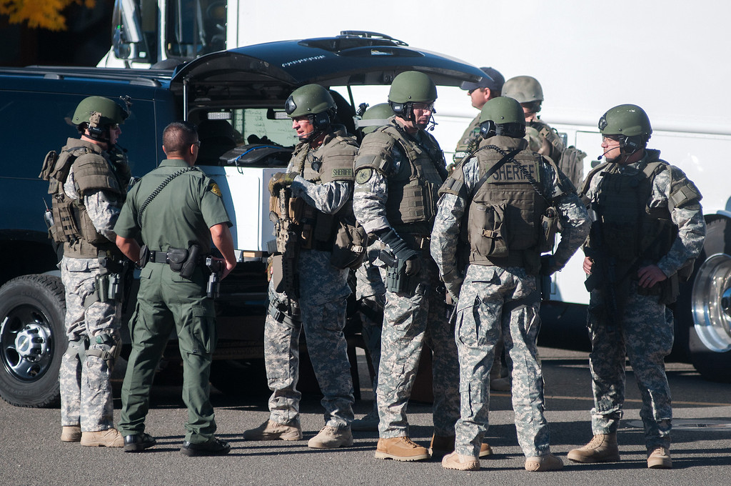 Description of . Swat team members secure the scene near Sparks Middle School in Sparks, Nev., after a shooting there on Monday, Oct. 21, 2013.  Authorities are reporting that two people were killed and two wounded at the Nevada middle school. (AP Photo/Kevin Clifford)