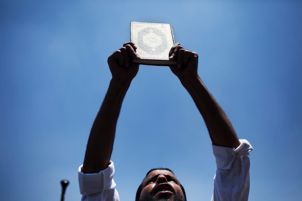 Description of . A supporter of ousted Egyptian President Mohammed Morsi holds a Quran while chanting slogans supporting Morsi during a protest in Cairo University, in Giza, Egypt, Friday, July 5, 2013. Tens of thousands, mainly Islamists, chanted