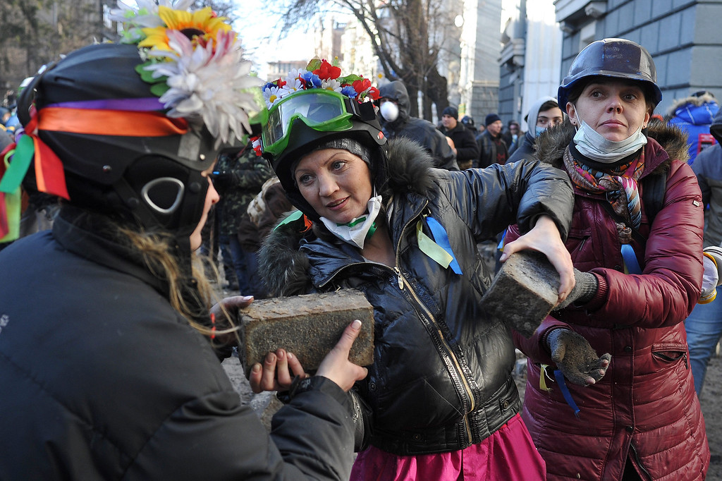 Description of . Women pass stones to protesters during an anti-government protest in downtown Kiev, Ukraine, 18 February 2014. A least three protesters were killed in clashes with police on 18 February, Ukrainian opposition activists say.   EPA/ALEXEY FURMAN
