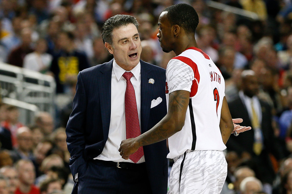 Description of . ATLANTA, GA - APRIL 06:  Head coach Rick Pitino of the Louisville Cardinals talks with Russ Smith #2 in the first half against the Wichita State Shockers during the 2013 NCAA Men's Final Four Semifinal at the Georgia Dome on April 6, 2013 in Atlanta, Georgia.  (Photo by Kevin C. Cox/Getty Images)