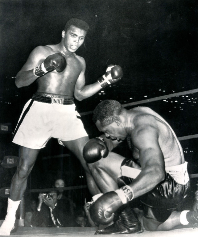 Description of . LOS ANGELES, Nov.15, 1962--END OF THE LINE FOR ARCHIE--Down on one knee, Archie Moore reaches the end of his gallant ring career in Los Angeles tonight as young Cassius Clay stands over him, winner by a technical knockout in the fourth round of a scheduled 12-round fight.  Moore went down three times before the referee, Tommy Hart, ended the fight.    Credit: AP