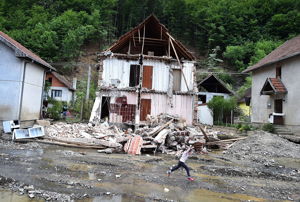 Description of . A child jumps over water near a house damaged by flooding and landslides in Krupanj, some 130 kilometers south west of Belgrade, on May 20, 2014, after the western Serbian town was hit with floods and landslides, cutting it off for four days. Serbia declared three days of national mourning on May 20 as the death toll from the worst flood to hit the Balkans in living memory rose and health officials warned of a possible epidemic. AFP PHOTO / ANDREJ  ISAKOVIC/AFP/Getty Images
