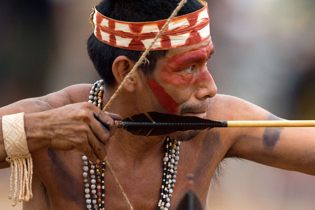 Description of . A Brazilian indigenous man of the Maiorona tribe takes part in the bow and arrow competition during the XII International Games of Indigenous Peoples in Cuiaba, Mato Grosso state, Brazil on November 12, 2013. AFP PHOTO / Christophe SIMON/AFP/Getty Images