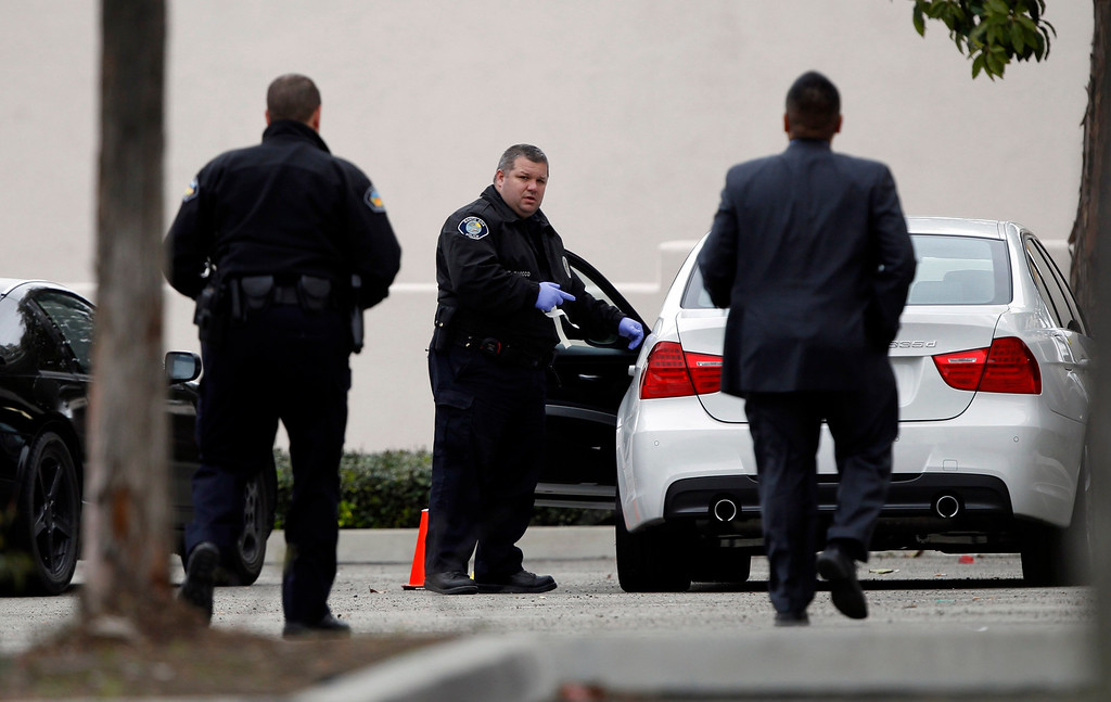. Police authorities process a stolen car in the parking lot of a Tustin computer store, after a gunman went on a shooting spree in suburban southern California, February 19, 2013.  REUTERS/Alex Gallardo
