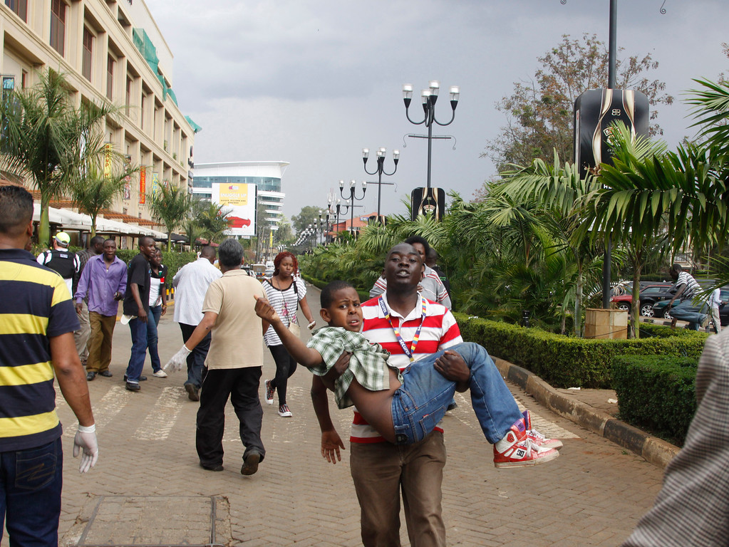 Description of . A rescue worker helps a child outside the Westgate Mall in Nairobi, Kenya Saturday, Sept. 21, 2013, after gunmen threw grenades and opened fire during an attack that left multiple dead and dozens wounded.  (AP Photo/Khalil Senosi)