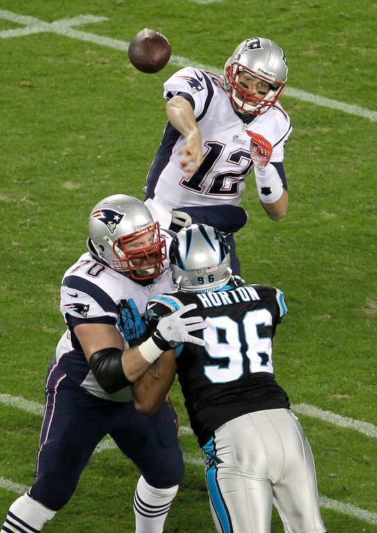 . New England Patriots\' Tom Brady (12) throws a pass under pressure from Carolina Panthers\' Wes Horton (96) during the first half of an NFL football game in Charlotte, N.C., Monday, Nov. 18, 2013. (AP Photo/Bob Leverone)