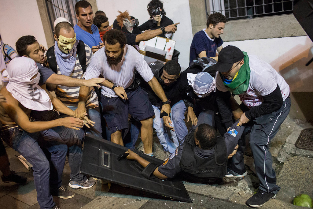 Description of . Protesters try to help a police officer after he clashed with others during a protest in Rio de Janeiro, Brazil, Monday, June 17, 2013. Officers in Rio fired tear gas and rubber bullets when a group of protesters invaded the state legislative assembly and threw rocks and flares at police as protesters massed in at least seven Brazilian cities Monday for another round of demonstrations voicing disgruntlement about life in the country, raising questions about security during big events like the current Confederations Cup and a papal visit next month.  (AP Photo/Felipe Dana)