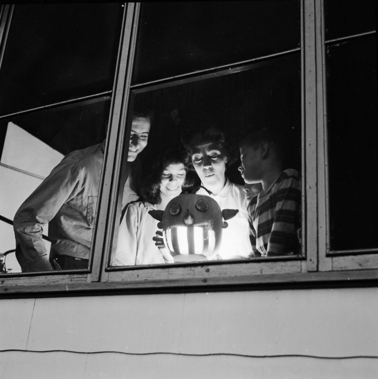 Description of . circa 1955:  An American family with a carved pumpkin illuminated by a candle to celebrate Halloween.  (Photo by Sherman/Three Lions/Getty Images)