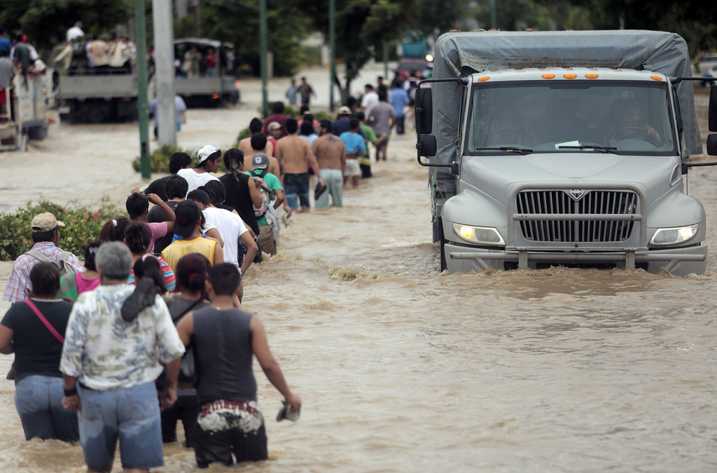 Description of . Residents and tourists wade through a flooded street in Acapulco, Guerrero state, Mexico, on September 17, 2013 as heavy rains hit the country. Mexican authorities scrambled Tuesday to launch an air lift to evacuate tens of thousands of tourists stranded amid floods in the resort of Acapulco following a pair of deadly storms. The official death toll rose to 47 after the tropical storms, Ingrid and Manuel, swarmed large swaths of the country during a three-day holiday weekend, sparking landslides and causing rivers to overflow in several states. Pedro PARDO/AFP/Getty Images