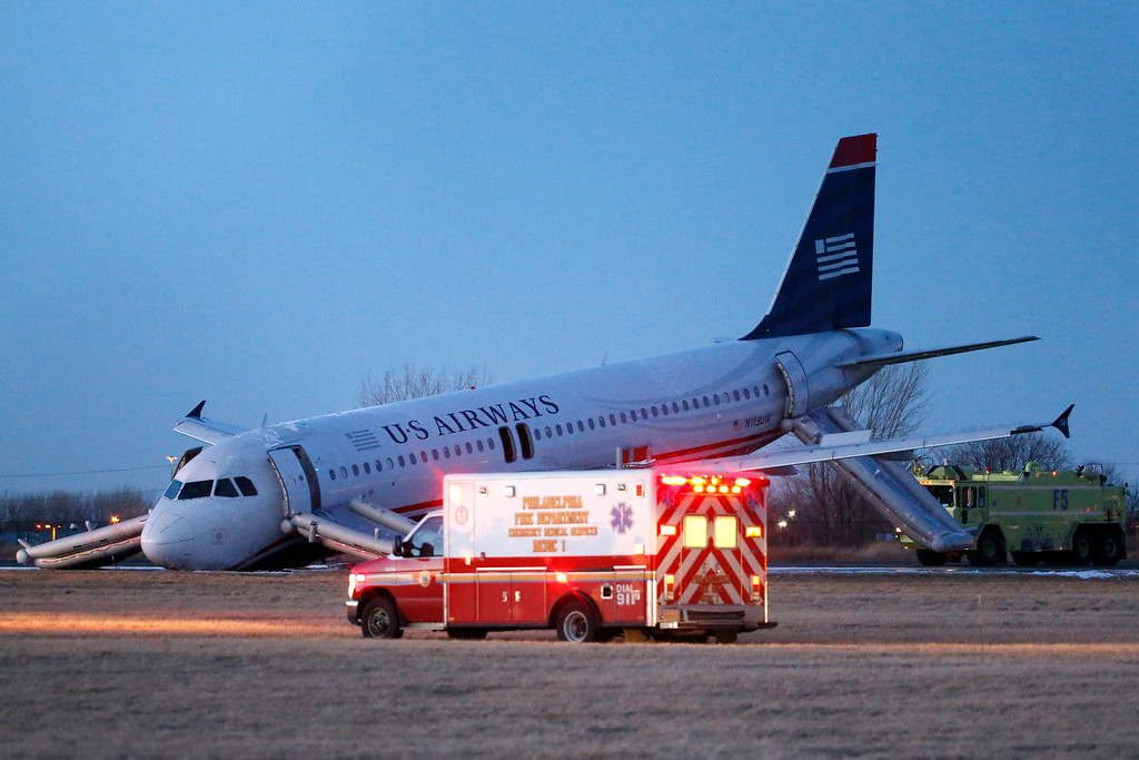 Description of . Emergency vehicles drive past a damaged US Airways jet at the end of a runway at the Philadelphia International Airport, Thursday, March 13, 2014, in Philadelphia. Airline officials said the flight was heading to Fort Lauderdale, Fla., when the pilot was forced to abort takeoff around 6:30 p.m., after the front landing gear failed. An airport spokeswoman said no injuries have been reported. (AP Photo/Matt Slocum)