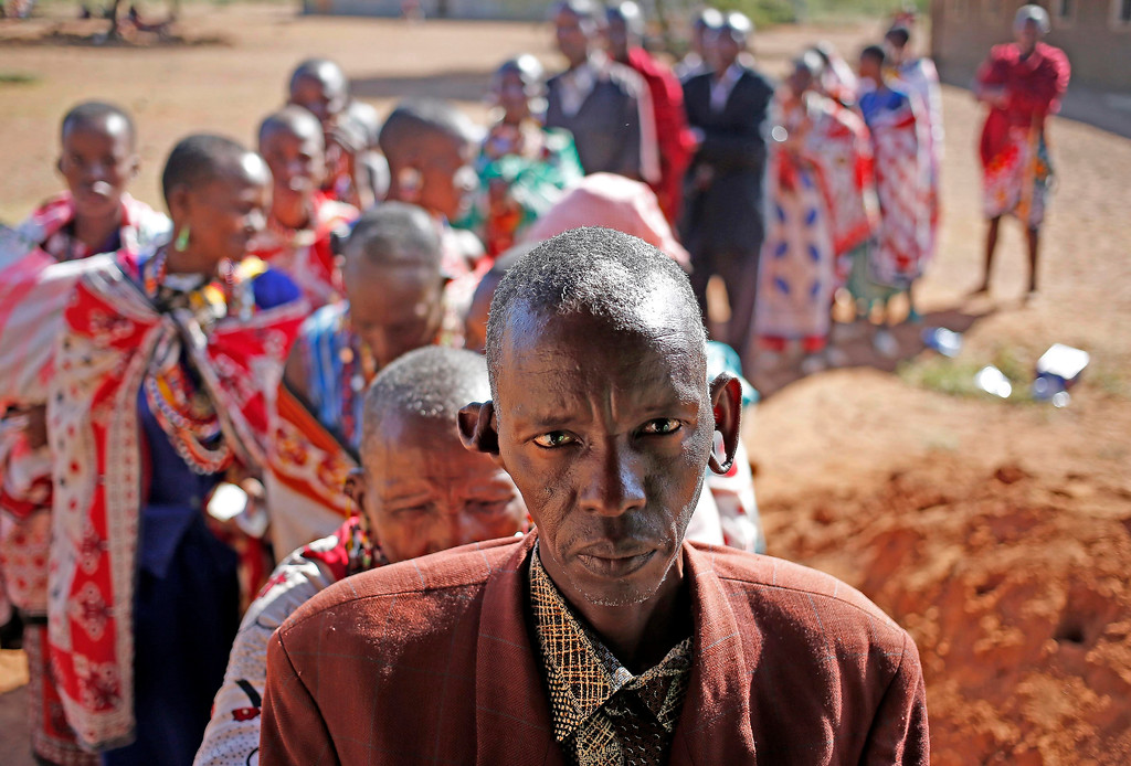 Description of . Masai wait to cast ballot papers outside a polling station during the presidential and parliamentary elections near town of Magadi some 85 km (53 miles) south of Nairobi. REUTERS/Goran Tomasevic