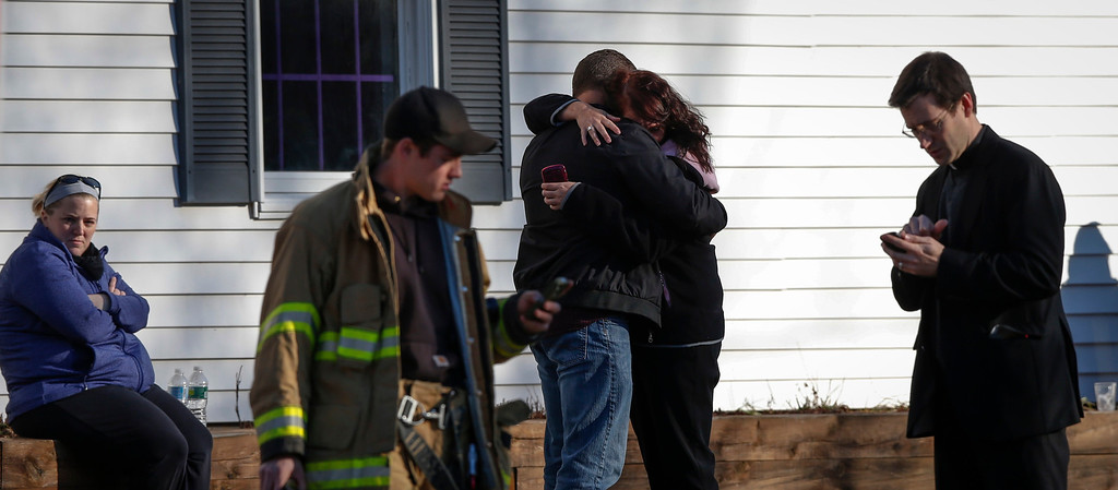 Description of . Family members embrace near Sandy Hook Elementary School, where a gunman opened fire on school children and staff in Newtown, Connecticut December 14, 2012. A heavily armed gunman opened fire on school children and staff at a Connecticut elementary school on Friday, killing at least 26 people, including 18 children, in the latest in a series of shooting rampages that have tormented the United States this year.     REUTERS/Adrees Latif