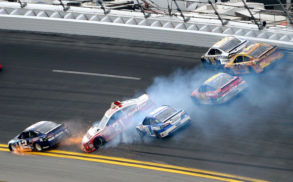 Description of . Trevor Bayne (21) spins in Turn 1 as Brad Keselowski (2) hits the apron and Carl Edwards (99), Scott Speed (95), Josh Wise (35) and Austin Dillon (33) try to avoid them during the NASCAR Daytona 500 Sprint Cup Series auto race at Daytona International Speedway in Daytona Beach, Fla., Sunday, Feb. 24, 2013. (AP Photo/Phelan M. Ebenhack)