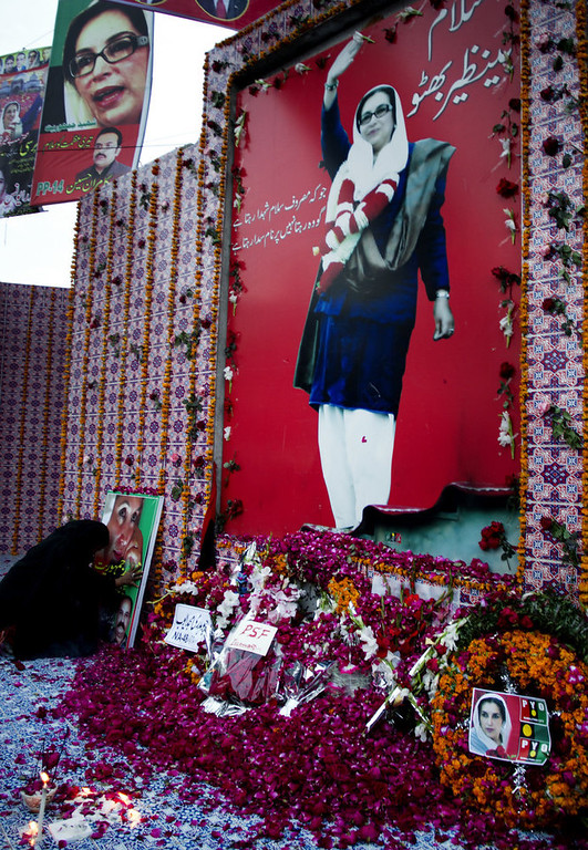 Description of . A supporter of Pakistan's assassinated leader Benazir Bhutto sits near a picture of her to pay tribute on her fifth anniversary in Rawalpindi, Pakistan,  Thursday, Dec. 27, 2012. The 24-year-old son of former Pakistani Prime Minister Benazir Bhutto has launched his political career at his ancestral place Larkana, with a fiery speech on the fifth anniversary of his mother's assassination. (AP Photo/B.K. Bangash)