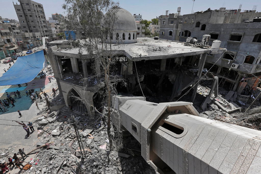 Description of . A fallen minaret, bottom right, is seen as Palestinians inspect the damage to the Al-Sousi mosque, that was destroyed in an Israel strike, at Shati refugee camp in the northern Gaza Strip, Wednesday, July 30, 2014. Israeli aircraft struck dozens of Gaza sites on Wednesday, including five mosques it said were being used by militants, while several other areas came under tank fire. (AP Photo/Lefteris Pitarakis)
