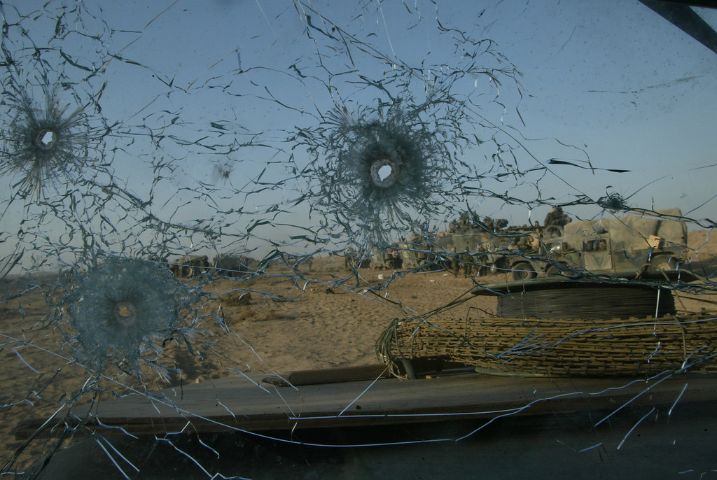 Description of . Bullet holes riddle the windshield of a U.S. Marine humvee from Task Force Tarawa March 23, 2003 in the southern Iraqi city of Nasiriyah. The Marines suffered a number of deaths and casualties during gun battles throughout the city. (Photo by Joe Raedle/Getty Images)