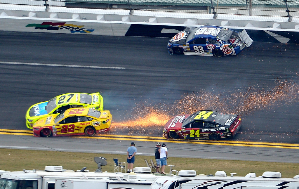Description of . Travis Kvapil (93) hits the wall as Paul Menard (27) and Joey Logano (22) collide, sending sparks on Jeff Gordon (24), between Turns 1 and 2 on the final lap of the NASCAR Daytona 500 Sprint Cup Series auto race at Daytona International Speedway in Daytona Beach, Fla., Sunday, Feb. 24, 2013. (AP Photo/Phelan M. Ebenhack)