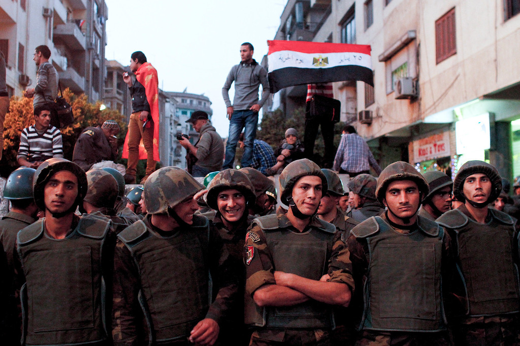 . Members of the Egyptian Republican Guard stand sentinel behind a barrier near the presidential palace in Cairo, Dec. 9, 2012. Hundreds of Egyptians continued to protest Sunday against President Mohammed Morsi\'s decision to keep the referendum on a disputed draft constitution scheduled for next week. (Tara Todras-Whitehill/The New York Times)