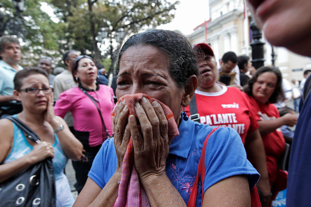 Description of . A supporter of Venezuela's President Hugo Chavez cries as she learns that Chavez has died through an announcement by the vice president in Caracas, Venezuela, Tuesday, March 5, 2013. Venezuela's Vice President Nicolas Maduro announced that Chavez died on Tuesday at age 58 after a nearly two-year bout with cancer. During more than 14 years in office, Chavez routinely challenged the status quo at home and internationally. He polarized Venezuelans with his confrontational and domineering style, yet was also a masterful communicator and strategist who tapped into Venezuelan nationalism to win broad support, particularly among the poor. (AP Photo/Ariana Cubillos)