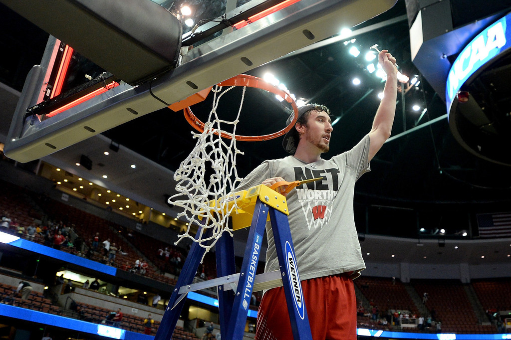 Description of . Frank Kaminsky #44 of the Wisconsin Badgers cuts down the net after defeating the Arizona Wildcats 64-63 in overtime during the West Regional Final of the 2014 NCAA Men's Basketball Tournament at the Honda Center on March 29, 2014 in Anaheim, California.  (Photo by Harry How/Getty Images)