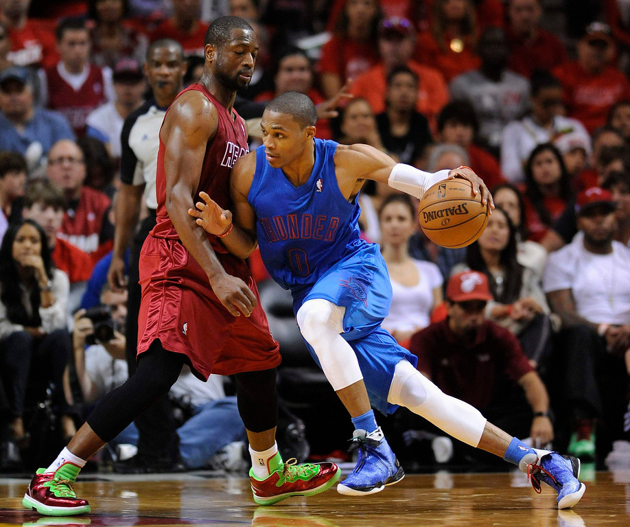 Description of . Oklahoma City Thunder's Russell Westbrook (R) is defended by Miami Heat's Dwyane Wade (L) during the first half of their NBA basketball game in Miami, Florida, December 25, 2012. REUTERS/Rhona Wise