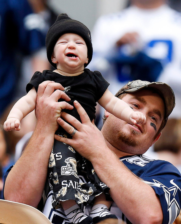 . A young New Orleans Saints fan is held by a Dallas Cowboys fan during the second half of an NFL football game on Sunday, Dec. 23, 2012, in Arlington, Texas. (AP Photo/Sharon Ellman)