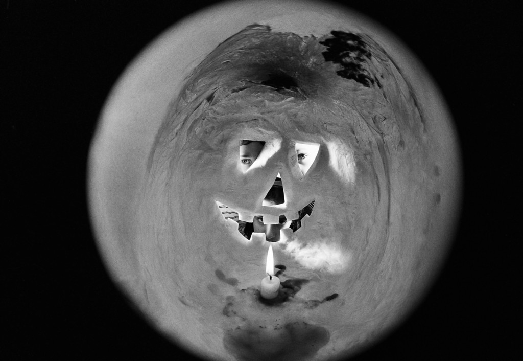 Description of . Pictured here is the inside of a pumpkin, all set up for Halloween with a candle, Oct. 20, 1964. The three youngsters whose eyes are looking from the other side see a 180 degree fisheye camera and a cut out in the back of the pumpkin. (AP Photo/Ruben Goldberg)