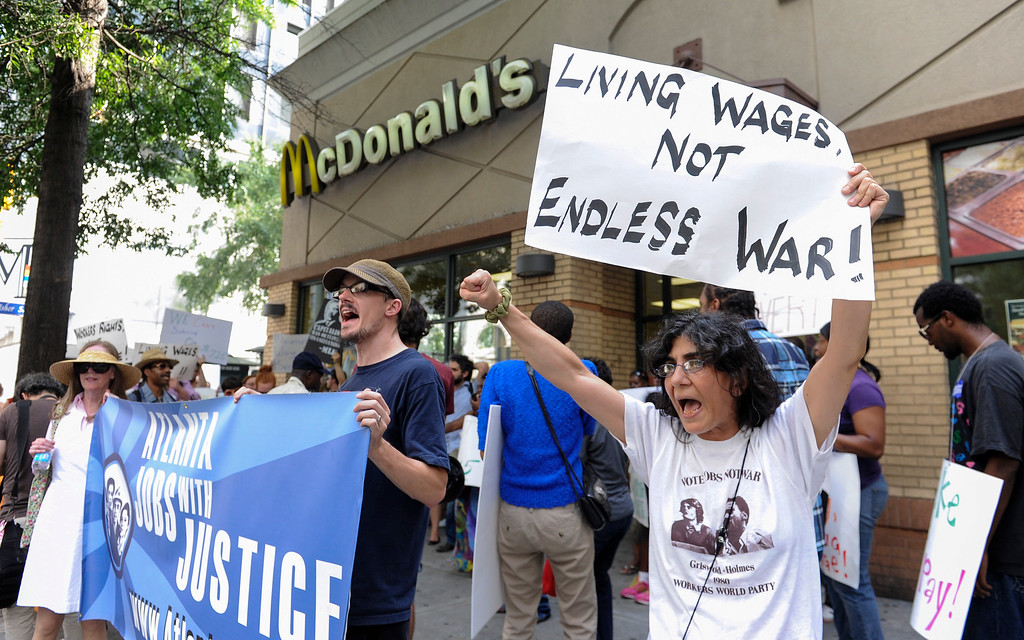 Description of . Azi Ebrahimi, right, demonstrates for higher wages for fast food industry workers during a one day strike coinciding with strikes at other fast food restaurants across the country, Thursday, Aug. 29, 2013, in Atlanta. (AP Photo/John Amis)
